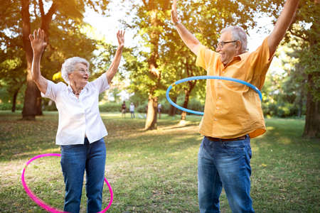 Happy and funny senior couple playing hulahop in park