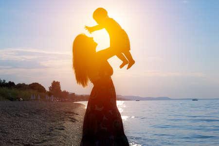 夕暮れ時のビーチで幸せな素敵な家族母と子息子
