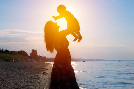 Happy lovely family mother and child son on beach at sunset