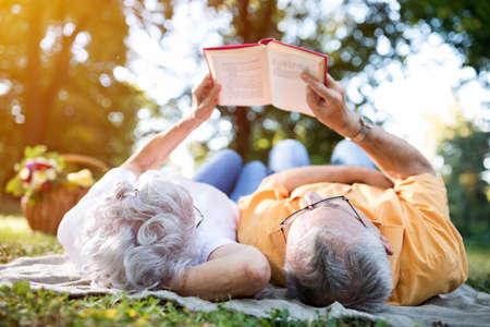 libros antiguos: Lovely altos pareja descansando en el parque, leyendo un libro