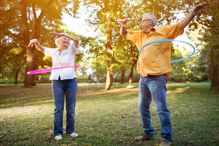 Happy and funny senior couple playing hulahop in park Imagens - 62889643