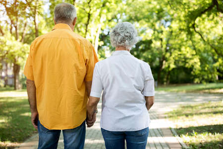 Old senior couple together walk through the park