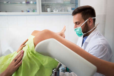 Young professional gynecologist exam his patient at clinic