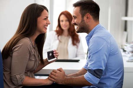超音波を保持している、クリニックで彼女の夫と手をつないでの母