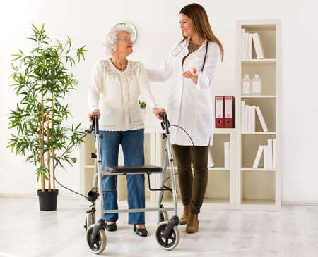 frailty: Senior woman with walker on consultation with the doctor, in ambulance Stock Photo