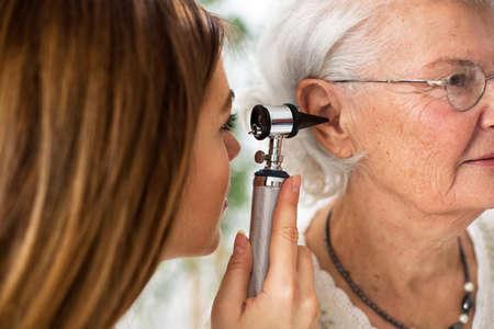 oido: Otoscopio médico sosteniendo y examinando el oído de la mujer mayor en ambulancia