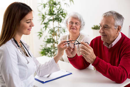 shortsighted: Doctor ophthalmologist giving glasses to patient after eyes exam at clinic Stock Photo
