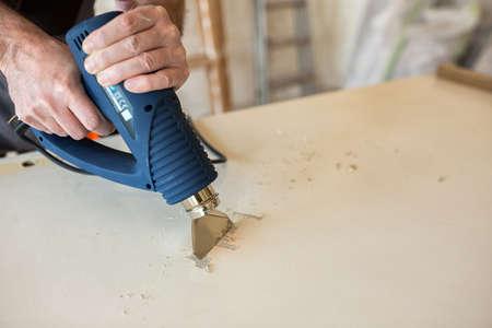 Worker repairs the door in a carpenters workshop, closeup Stock Photo