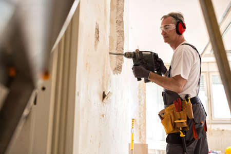 건설 현장, 근접 촬영에서 드릴 사용하여 수석 작업자