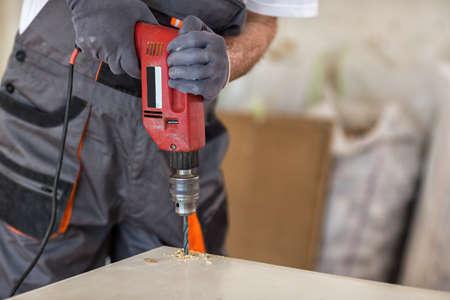Carpenter used drills  in reparation of old doors in workshop