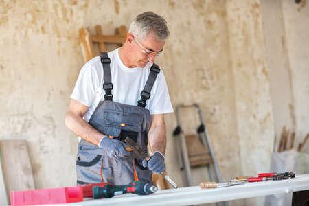Carpenter restores old door in workshop, close up