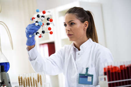 Young woman holding type of modified molecular wheat, doing research alt pro lab