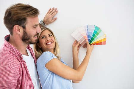 feliz pareja joven elegir colores para pintar su hogar