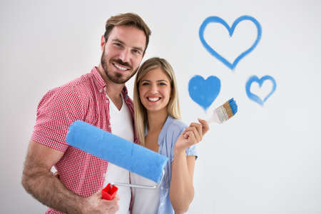 Young happy couple painting new home, lovely smiling success Stock Photo