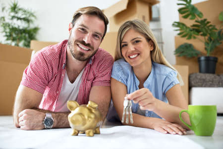 Young smiling couple holding keys at new apartment
