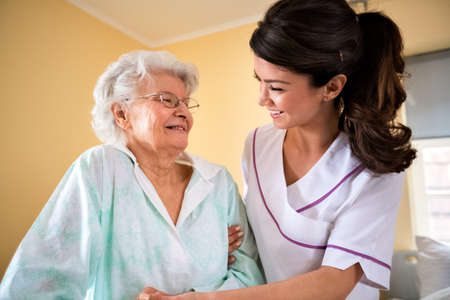 Care of the elderly at nursing home, nurse helps to senior woman to walk