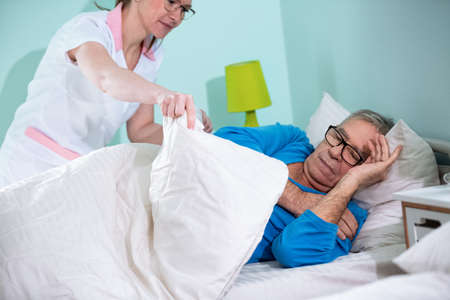 Nurse take care of patient at nursing home, cover old man with a blanket Stock Photo