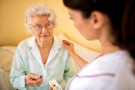 Sad alone senior woman taking a drog from daily box  while nurse brings to her