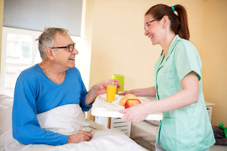 Young smiling nurse brings breakfast to senior patient at nursing home Stock Photo