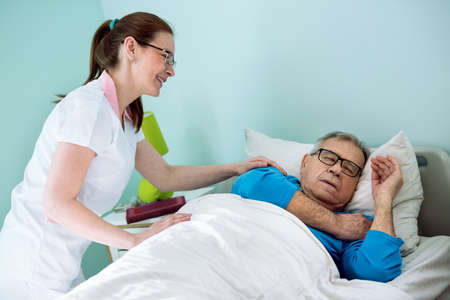Nice smiling nurse looking at patient who sleeping and dreaming at nursing home, care for the elderly people