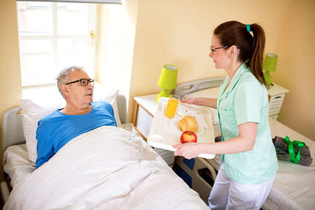 Compele a favor at nursing home, nurse brings fresh food for senior man Stock Photo