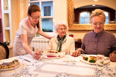 Nice careful nurse sets a table for dinner to patients at nursing home