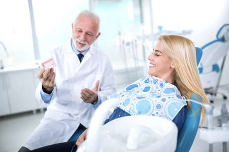 Dentist shows the patient the results of prosthetics in the dental practice