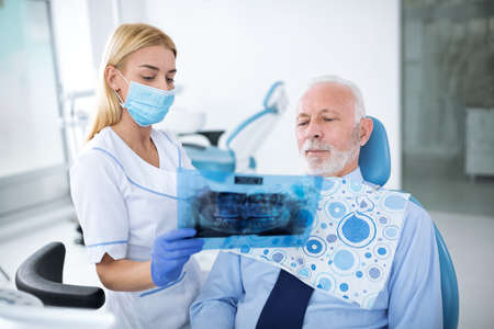 A young woman's dentist shows X-ray patient, she has protective gloves Zdjęcie Seryjne - 97574754