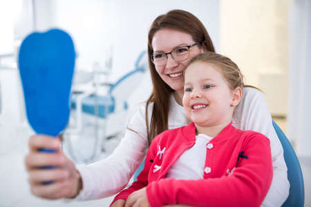 Mom and daughter looks teeth at mirror in dentists office
