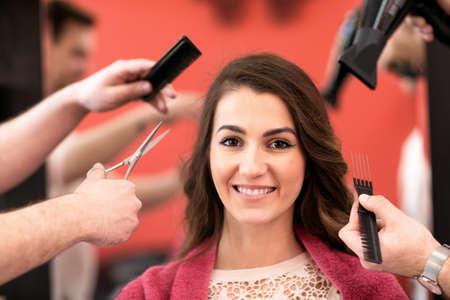 Portrait of beautiful young woman getting haircut at luxury beauty salon Stock Photo