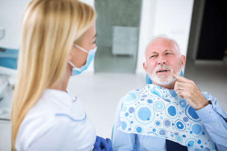 Patient shows dentist where exactly there is pain in his teeth Stock Photo