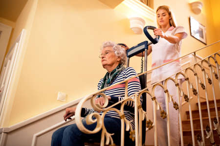 Nurse using machine for climbing to the stairs and helps old mature senior disabled woman close up