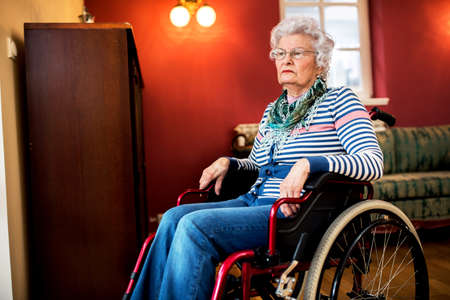 Forgotten by the family, sad senior woman at wheelchair at nursing home