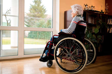 Loneliness senior woman sitting in wheelchair at nursing home, forgotten by the family