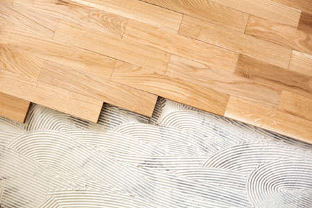 A closeup of subfloor mixture and assembled parquet plates in the working environment