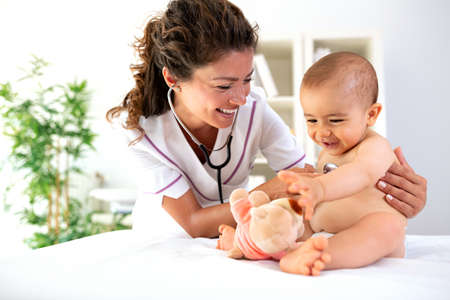 A pediatrician distracting her patient with a teddy bear so she can check his heartbeat much easier