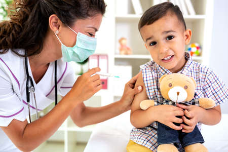 Child receiving a vaccine dose  accompanied with his friend teddy bear