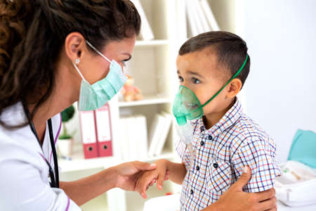 Caring pediatrician giving oxygen to a little child making sure he recovers fast as possible
