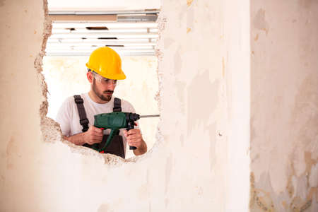 Worker wearing a yellow protective helmet drilling holes in the wall