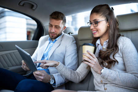 Businesswoman drinking a coffee as her partner looks in his tablet and showing her some interesting things