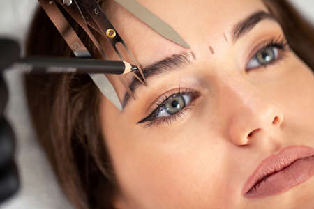 Cosmetician preparing to make a legit appearance of naturally full brows on the face of a pretty young woman