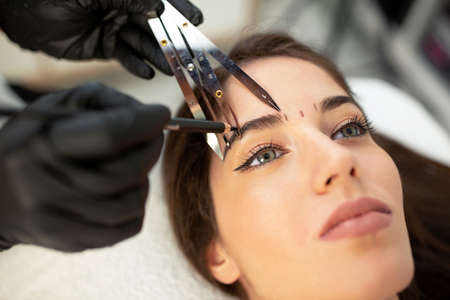 Using cosmetics tools for taking the correct measure of future eyebrows done with microblading technique Stock Photo