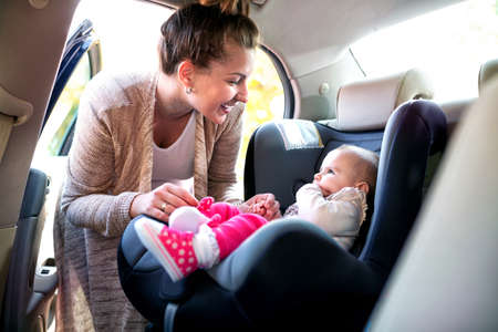 Smiling mom and her cute daughter preparing to go for a ride Archivio Fotografico