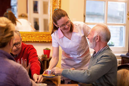 Nurse serving tea in the retirement home while occupants sit at the table