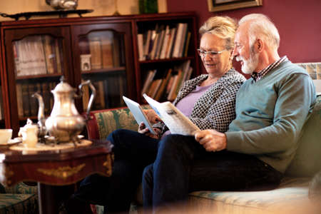 Senior people making comparison between online news and news from the newspapers by reading both of them