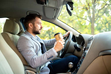 Young handsome man enjoys his coffee while cruising through the woods