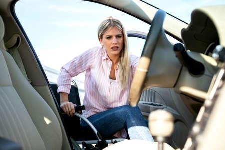 Entrar en su automóvil puede ser un poco complicado si tiene una discapacidad física, una joven rubia con pérdida de función de las piernas