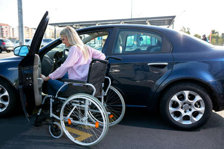 Image of young disabled woman trying to reach her car on the parking lot