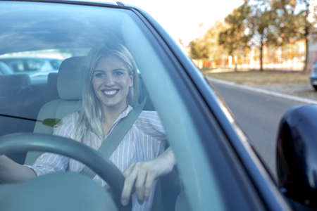 Attractive blonde girl observed through the windshield of her car