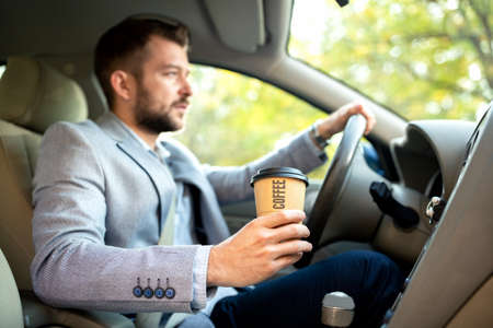 One hand on the steering wheel and other holding a cup of coffee, no sleep mode Stock Photo - 118085455